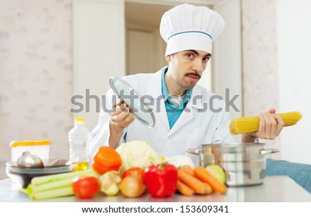 Positive cook man cooking with pasta at kitchen - stock photo