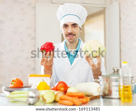 Positive cook man in toque with vegetables in kitchen - stock photo