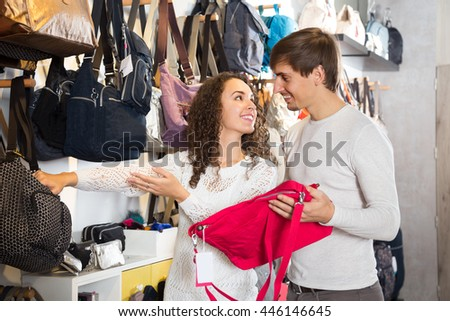 Positive couple looking at stylish female handbags in store - stock photo