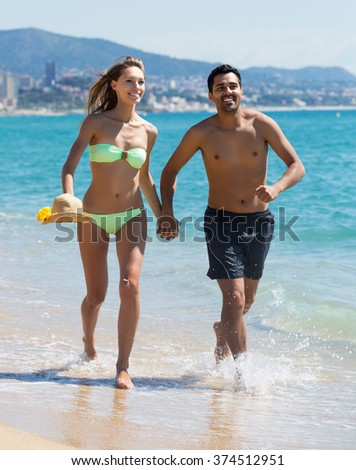 Positive couple running on the beach