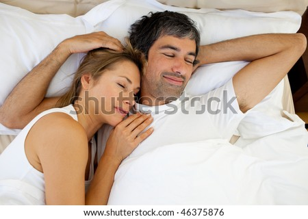 Positive couple sleeping lying in bed - stock photo