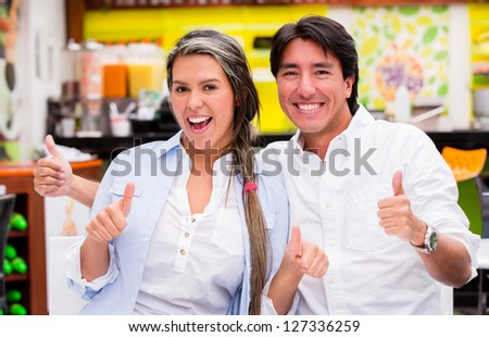 Positive couple with thumbs up looking happy - stock photo