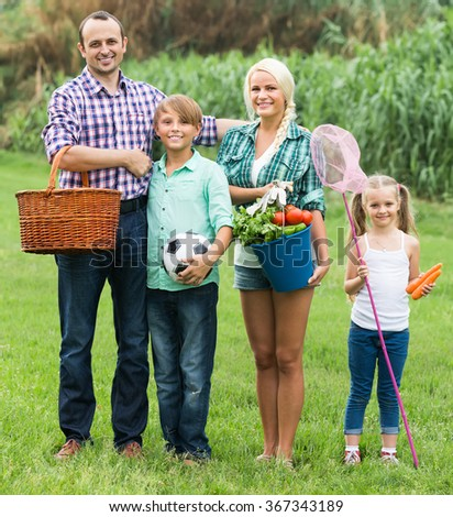 Positive couple with two children having rest at countryside at summer day  - stock photo