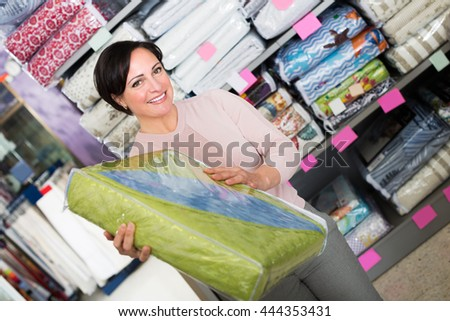 Positive customer handles bedspread near textiles shelves inside - stock photo