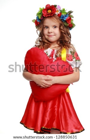 Positive cute girl in a bright Ukrainian national costume/little girl with bright red heart symbol on white background