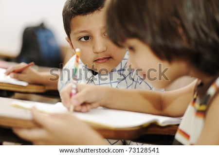 Positive cute kid in the school, writing on table, red apple in front of him - stock photo