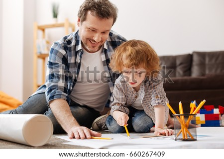 Positive delighted male person spending time with his son