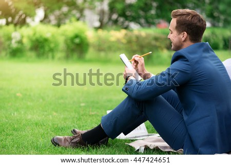 Positive delighted smiling man sitting on the grass