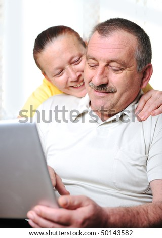 Positive elderly couple with laptop in hands - stock photo