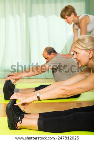 Positive elderly couple worming up at gym with female trainer  - stock photo