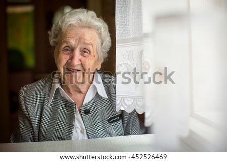 Positive elderly woman sitting in the room. - stock photo