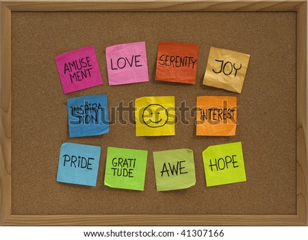 positive emotions concept - color sticky notes around smiley on cork bulletin board - stock photo