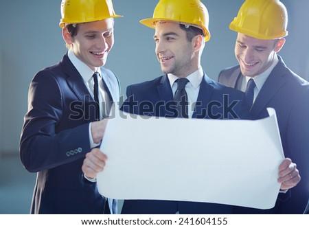 Positive engineers examining blueprint - stock photo