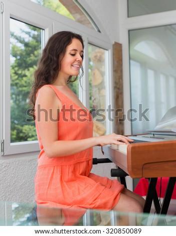 Positive european girl having piano class in home interior - stock photo