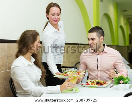 Positive european people ordered vegetarian food at restaurant - stock photo