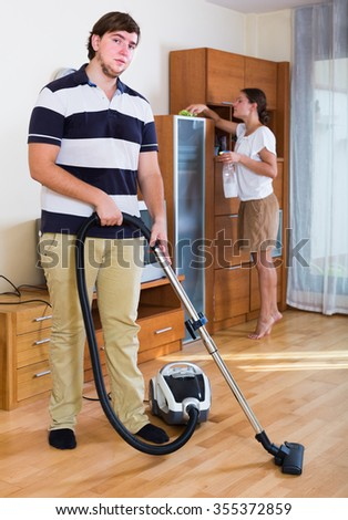 Positive family couple doing regular clean-up at home - stock photo