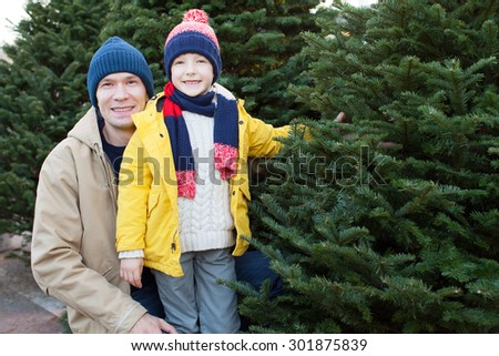 positive family of father and his son christmas tree shopping at winter time - Christmas Tree Shopping