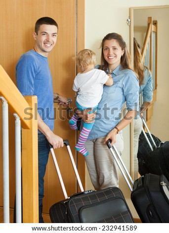 positive family travelers with luggage in home going on holiday - stock photo