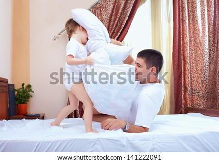 positive father and son having fun at home, pillow fight - stock photo