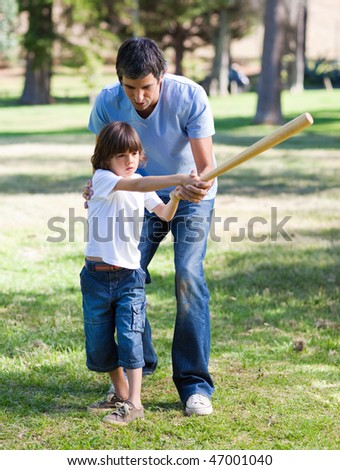 Positive father teaching baseball to his son in the park - stock photo