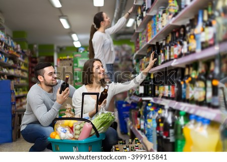 Positive female and male buying beverages for dinner at food shop - stock photo