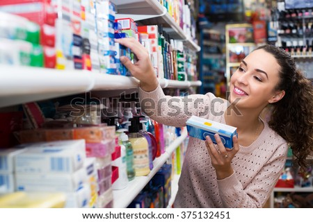 Positive female buying toothpaste for sensitive teeth in store - stock photo
