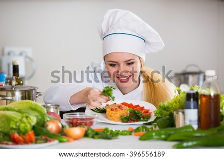 Positive female chef posing with plate of salad and cheese