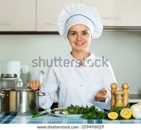 Positive female chef working with fish in kitchen