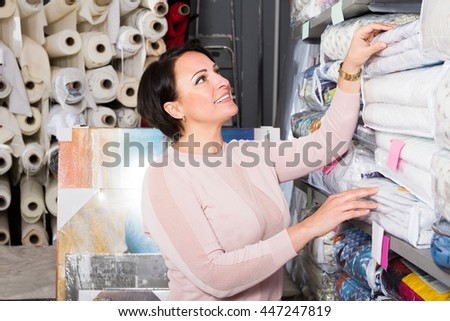 Positive female customer handles bedspread near textiles shelves inside - stock photo