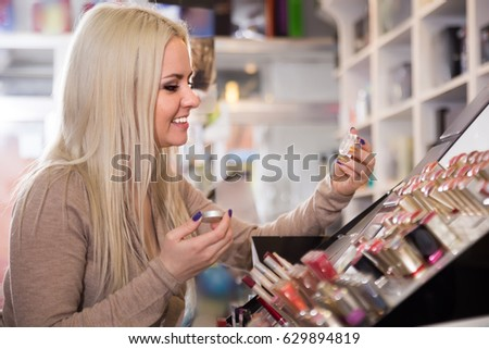 Positive female customer selecting beauty treatment in makeup section