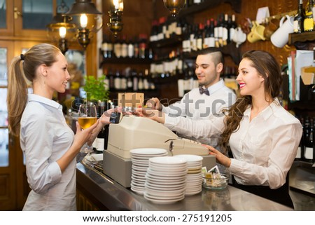 Positive female drinking wine at counter and chatting with bartenders inside
