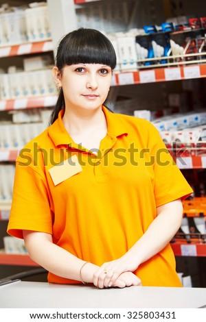 Positive female seller or shop assistant portrait  in hardware supermarket store - stock photo