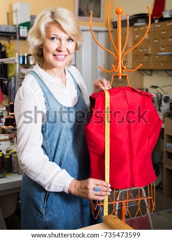 positive Female tailor working near mannequin in sewing workshop