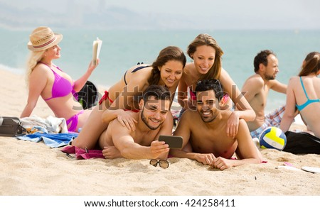 Positive friendly people making mutual photo at sandy beach