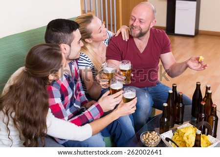 Positive friends hanging out with beer and snacks in the home  - stock photo