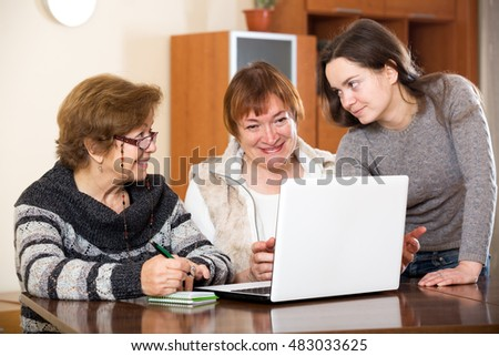 Positive girl helping mature women buy something in web. Focus on the left woman