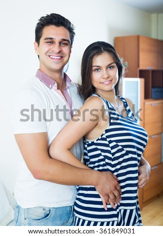 Positive girlfriend and boyfriend cuddling at home - stock photo