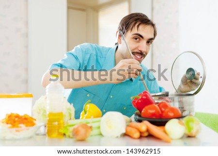 Positive guy doing vegetarian lunch at kitchen - stock photo