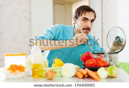 Positive guy doing veggy lunch at kitchen - stock photo