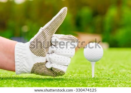 Positive hand gesture near the golf ball on a tee - stock photo