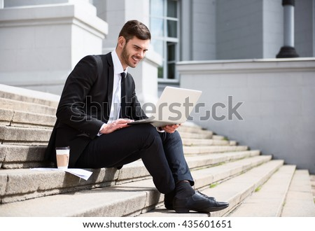 Positive handsome businessman sitting on the footsteps - stock photo
