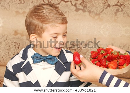 Positive handsome  small style boy with fashion hairdo looking at big juicy ripe strawberries and smiling - stock photo
