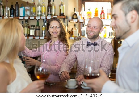 Positive happy bartender entertaining guests at bar counter  - stock photo