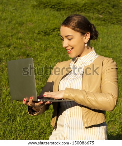 Positive happy brunette working on a laptop - stock photo