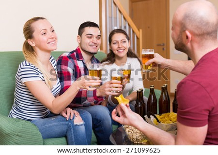 Positive happy friends hanging out with beer and snacks at the home  - stock photo