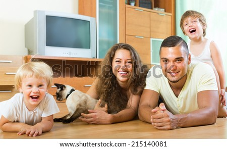 Positive happy young family of four laying on the floor at home with kitten - stock photo