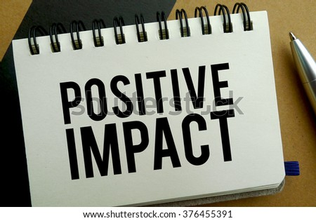 Positive impact memo written on a notebook with pen