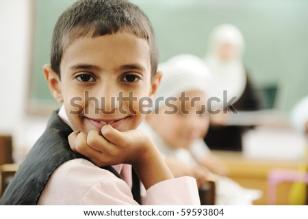 Positive kid in classroom smiling and looking in camera - stock photo