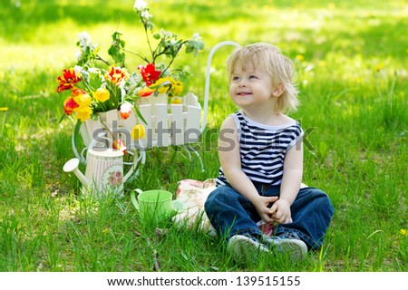 Positive kid sitting on the fresh green grass in the garden near decorative wooden wheelbarrow full of flowers