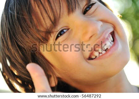Positive kid with his thumb up, closeup - stock photo